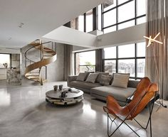 sol de salon en béton ciré et escaliers en colimaçon en bois comme oeuvre d'art