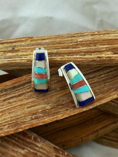 This is a pair of stunning vintage Zuni sterling silver earrings inlaid with genuine lapis lazuli, turquoise, coral, and mother of Pearl that are