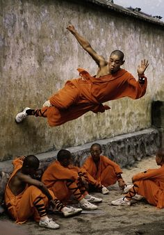 Chinese martial art: Shaolin Kungfu. At first I was like there are two pictures there, but then I was like nope that's a man on the wall over people.