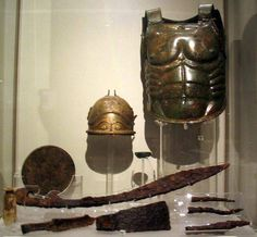 """The complete armaments and goods from 'The Tomb of the Warrior"""", from Lanuvium (modern Lanuvio). While Italic, the items show a Greek cultural influence, which makes sense since the cult of the Dioskuri was heavily prevelant during this time period in Italy. """"Of the arms found in the tomb are exhibited: bronze anatomic breastplate, parade helmet of bronze, silver, gold, and glass paste, axe, a sword, three spear heads."""" 465 BCE"""