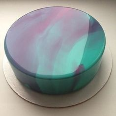 Mirror Glaze Recipe: 20 g Gelatin Powder 120 g Water 300 g Corn Syrup/Glucose 300 g Sugar 150 g Water 200 g Sweetened Cond Milk 300 g Chocolate (White, Milk, Dark or a combination) Food Coloring Bloom the gelatin in the water. Boil the glucose, sugar & water. Remove from heat and add the gelatin. Add the cond milk. Pour over chocolate and immersion blend/buerre mix to remove air bubbles. Use at 35C/95F The marbling effect is with different color glazes poured together over the cake.