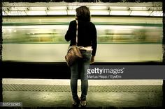 Foto stock : Rear View Of Woman Standing At Subway Station Against Moving Train