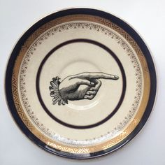 pointing hand: upcycled, altered vintage Myotts plate with waterslide decal in black, gold, and white