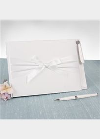 """Satin guest book features a cover hugged by wide satin, and finished off with a cheerful bow. Inside pages are lined with the word """"Guests"""" at the tops of each page. Coordinating pen holder is attached to the guest book, for your convenience. Guest Book measures 9 1/2"""" x 6 1/2"""" and pen stand is 4"""" square.Pen holds black ink. Available in White or Ivory."""