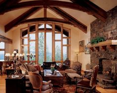 Living Room: Rustic Living Room With Stone Wall And Custom Windows. rustic living room. outdoor view living room. exposed beams ceiling. stone fireplace. reclaimed wood coffee table. brown leather chair. classic table lamp. wooden chest. custom window frame.