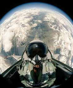 A Swiss Air Force F-5E Tiger II pilot takes a self-portrait with Earth in the background while his aircraft is in a vertical climb