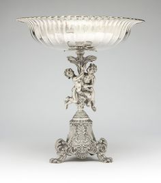 Italian Sterling silver compote by Messulam, After 1968, Milan,  the circular flaring gadrooned bowl with gold-washed interior supported by two cast cherubim grasping a foliate spray, over a shell, scroll and foliate tripartite base raised on paw feet.