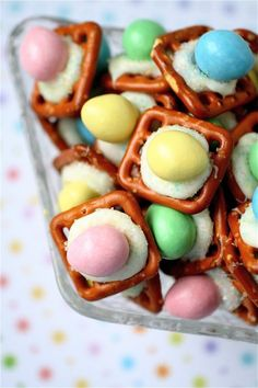 Easter Egg - Peanut M & M's, White chocolate Hershey Hugs and Snyders square pretzels.  Place one Hershey Hug onto a square pretzel on a cookie sheet.  Bake 7 minutes in 175 degree oven.  Remove from oven and quickly sprinkle with colored decorator sugar. Press a Peanut M&M into the melted Hershey Hug.