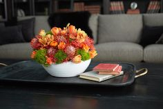 A simple white bowl serves as a container for a mix of colorful flowers.