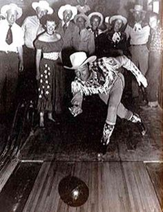 Roy Rogers tosses a bowling ball down the lanes at Pioneertown,while an avid audience of Dale, the Farr brothers and other folks look on.