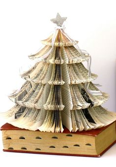 Old Book Christmas Tree. Made from an old book titled Music in Europe and the United States, it's topped with a silver glitter covered star, and white organza with silver cascading bows. The page edges have been stained with a brown paint wash. Book Christmas Tree, Book Tree, All Things Christmas, Christmas Fun, Vintage Christmas, Christmas Decorations, Holiday Tree, Xmas Trees, Christmas Ornaments