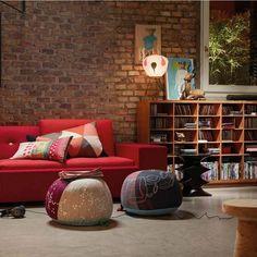 brique de parement rouge, canapé design en rouge, coussins décoratifs et poufs multicolores