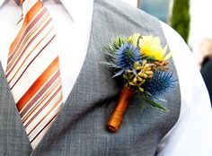 Boutonniere made with thistle, dahlia buds, seeded eucalyptus, orange dahlias and yellow ranunculus.
