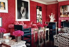 Thomas Britt channels a graphic, funky vibe in this living room bycontrasting the rougetones of the damask wallcovering with black and white furnishings and overscale artwork.