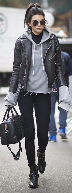 Kendall Jenner in black jeans, booties, a hoodie and a leather moto jacket…