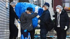 Police officers carry a sheet-covered computer from the apartment of abduction suspect Kabu Terauchi on Monday.