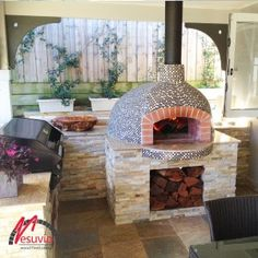 Vesuvio Wood Fired Oven – FVR100  This woodfired oven is the perfect feature in this alfresco outdoor kitchen area. The mixture of slate tiles, shale and black and white gloss mosaics gives a great contrast of textures and makes the oven just pop.  This area is truly inviting and the kitchen is equipped with bi-fold doors opening to this area to merge the indoors with the outdoors for the perfect entertaining area.