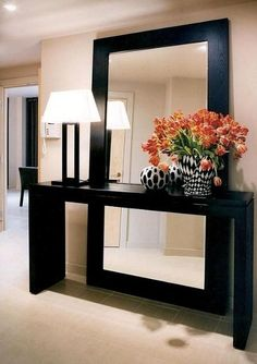 decoração de hall de entrada com aparador preto grande, luminária e vaso de flores preto e branco, espelho grande apoiado no chão