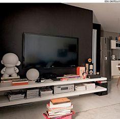 Ideia do arquiteto Mauricio Karam para disfarçar a TV: pinte a parede com uma cor escura.