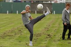 """Louis from One Direction playing soccer out side the Brisbane Entertainment center today , he managed to hit 3 ( parked ) cars with his soccer ball 4 times"""