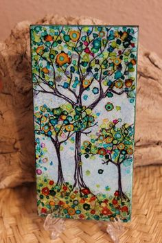 A whimsical and colorful trio of trees painted with alcohol inks on a rectangular ceramic tile spray coated for protection and durability. The sides and back are painted black with acrylic paint and spray coat.To take a break from making jewelry I started to paint ceramic tiles with