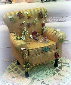 A miniature, upholstered chair becomes a pincushion for display brooches. Oversized props are great for store windows, but miniatures are ideal for displaying jewelry