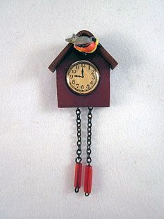 "Wonderful Hard Celluloid Cuckoo Clock.  This clock is 1"" tall without the chains, and 2-1/4"" tall with the chains at even lengths. It is 7/8"" wide x 1/4"" deep."