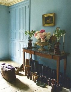 An inspiring entryway, painted blue and adorned with flowers.