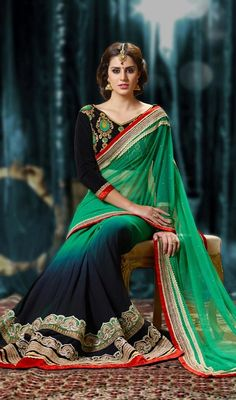 Allure the mass draping this black and emerald green shade georgette net half n half saree. The ethnic moti, resham and stones work to your attire adds a sign of beauty statement for your look. #ExtraordinaryTrendsetterSaree