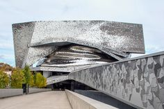 a spiraling aluminum form surrounds the central concert hall, contrasting an…