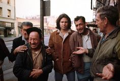 December 1969, Los Angeles, CA – Jim Morrison stands amidst a group of men outside the original Hard Rock Cafe in the skid row area of downtown L.A.  – Image by © Henry Diltz/Corbis]