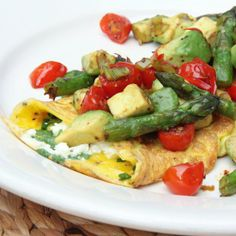 Fresh herb and feta omelet with warm avocado, asparagus, and cherry tomato salsa