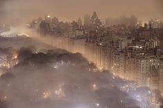 A 20-second long exposure photo captures an early morning fog drifting over Central Park in New York City