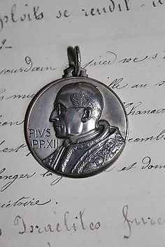 $50.00 on ebay comparable to the pendant we have. Gorgeous-French-vintage-religious-bronze-silver-medal-Pope-Pius-XII-pendant-20th
