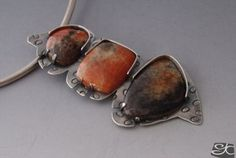 Handmade contemporary pendant in sterling silver with 3 Orange calcite cabochons set  with a 1/2 bezel and tabs. Textured and treated with a black 0patina to enhance the texture.