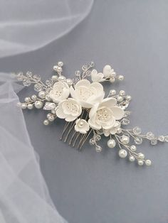 This beautiful handmade bridal hair comb made with pretty crystal elements, handcrafted flowers and white glass pearls. Complement most wedding hairstyles. It is the perfect bridal headpiece for that woman who wants to simply sparkle on her wedding day. DIMENSIONS: 6.5 x 2.5 (16 x 7 cm)
