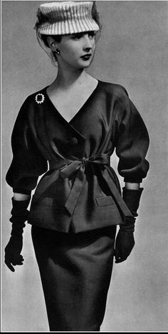 1956 Renée Breton in navy blue alpaca two-piece, top tied with same-fabric belt, white toque with navy voilette, by Christian Dior,
