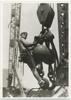 A worker riding on a crane hook