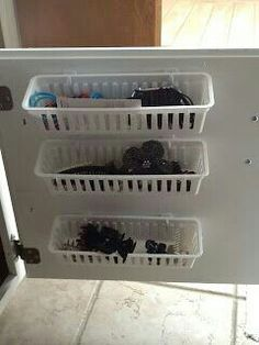 Add 3 basket (sold as set of three at Walmart or Dollar Tree) & attached to inner cabinet door with 3M hooks.   G;)
