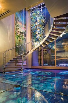 The foyer in Acqua Liana house has a water floor, a 24' water wall and a glass staircase.