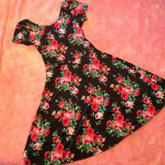"NWOT Floral Dress with Back Cutout NWOT. Black dress with floral pattern. Soft and stretchy, ""skater"" style with cute and sexy cutout in the back. Never worn, excellent condition. Perfect for spring and summer. Pinc brand. Size medium. Very pretty Pinc Dresses"