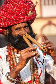 Rajasthani folk artist playing flute with his nose. Venue: Kala Ghoda Arts Festival 2012, Mumbai.