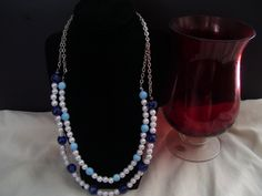 Double chained necklace with both dark and light blue beads. by…