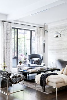 A cozy and neutral living space with modern floor lamp, patterned chair, and faux fur throw