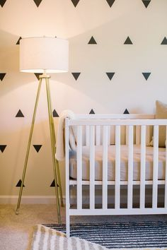 This beautiful nursery is neutral and modern! We love the modern brass floor lamp for added nursery lighting and style.