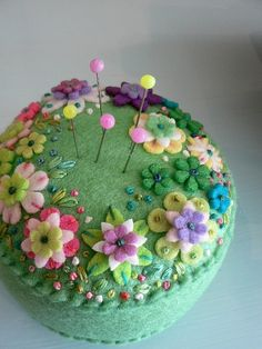 Felt pincushion with embroidery ... flowers must be punched rather than hand-cut, very spring-like.