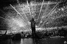 This photograph was clearly taken from the back of the stage during a concert, which automatically means that the photographer had permission to be there and was using a high ISO in order to properly capture the moment in such a high quality way. The black and white colouring of the photo also gives the photo a striking atmosphere, the juxtaposition of a light top and a dark bottom.