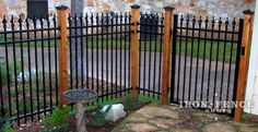 Our iron fence installed with beautiful stained wood posts.