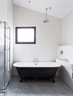 White subway tiles in bathroom with black and white tub