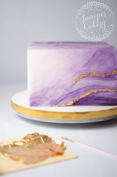 adding gold flakes to purple marbled cake